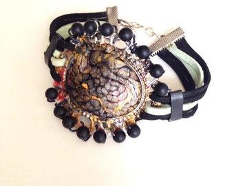 Bracelet black and green enamel, laces, black beads around
