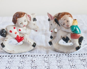 A pair of vintage hand painted girl and boy figurines, twin children riding rocking donkeys