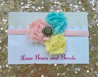 Blush pink, yellow, aqua blue headband with rhinestone center on pink glitter stretch elastic headband.