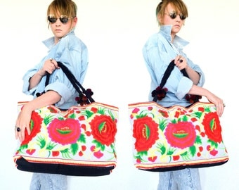 Rectangular white handbag embroidered with red and pink flowers.