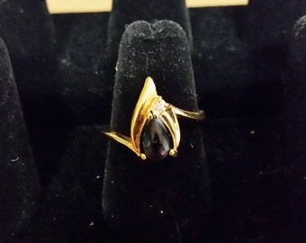 Gold tone ring with black stone