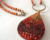 Textural Tribal Pendant Necklace: polymer clay, tear drop shaped, black, orange, yellow, gold, red, beaded