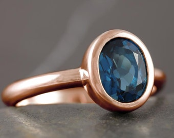 Solid gold solitaire engagement ring with London blue topaz