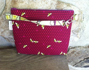 sofs offers a mid-size wristlet in berry bee.