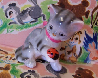 gray striped kitty with ladybug figurine