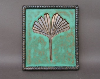 Embossed ginkgo leaf tile, glazed in metallic gold and copper patina, with oak hanger