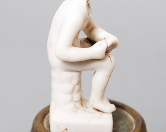 Antique porcelain figurine. Sitting man