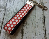 Red with white polka dots key fob wristlet on black cotton webbing with swivel lobster clasp