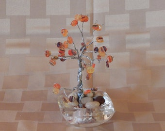 Tree sculpture with orange and yellow disk glass beads sitting in a clear glass base