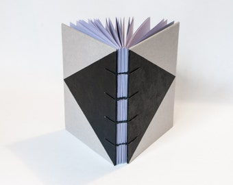 Coptic Bound Note Book - Lilac pages, grey front cover with hand painted triangle.112 A6 pages, 80gsm, opens flat. Geo, minimalist notebook.