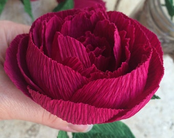 Deep red peonies, paper flowers, with green leaves