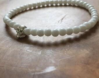 White Silver Skull: an elastic beaded bracelet with silvertone skull and white glass beads.