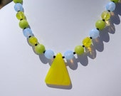 Pretty choker length necklace with an old African trade bead as a pendant and sparkly green, blue and yellow glass beads.