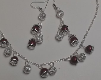 Silver necklace/earring set. Necklace with 7 Bordeaux Swarovski pearls and 6 silver hearts. Earrings of 3 pearls each between silver hearts
