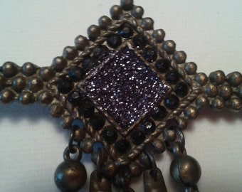Vintage 1930's geometric art deco brooch.  Brass metal jewelry peice decorated with glamorous black faceted stones and glitter. True