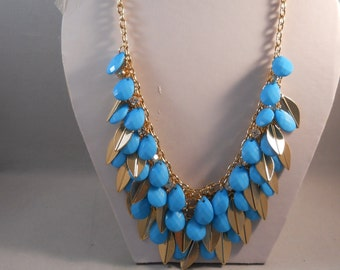 3 Row Bib Necklace with Blue Teardrop Beads and Gold Leaf Charms on a Gold Tone Chain