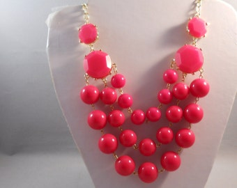 3 Row Bib Necklace with Deep Pink Beads in a Gold Tone Frame on a Gold Tone Chain