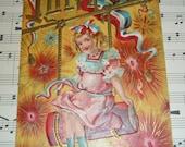 Pretty Little Girl in Pink Dress Sits on Firecracker Swing July 4th Antique Unused Embossed Postcard