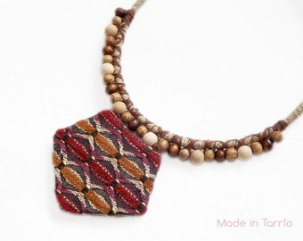 Arrow necklace, wooden ethnic lined burgundy cloth.