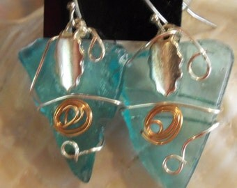 """Earrings.  Recycled turquoise glass wrapped in copper and sterling silver wire and hung on sterling french hooks.  Approx. 1 1/4"""" drop."""