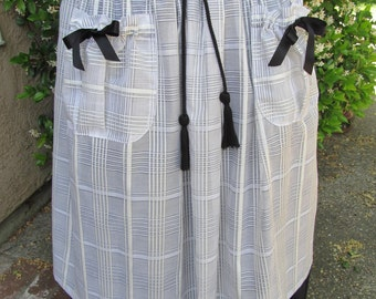 White cotton silk apron, black ties and tassels