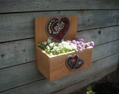 Solid cedar planter box with red mosaic heart design