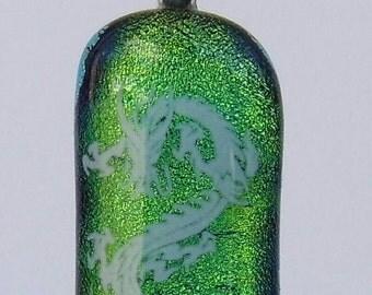 white enamel dragon on green dichroic glass pendant.