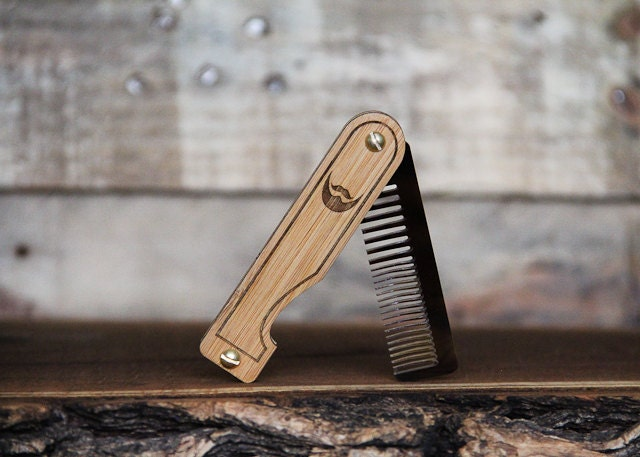 A handmade folding pocket wood comb for a beard