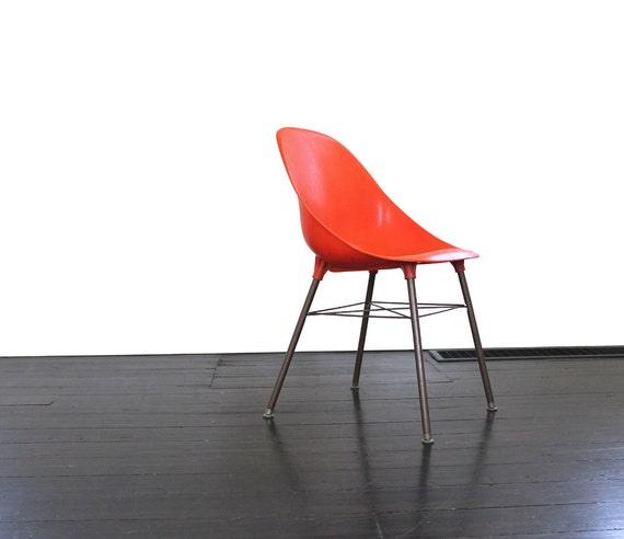 vintage plastic orange shell chair with metal legs
