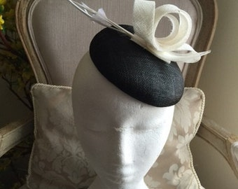 Stunning black round base fascinator with white sinamay loops and feathers. Gorgeous on!
