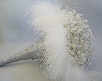wedding bouquet with opalescent beads on silver wire surrounded by feathers with a silver ribboned handle and diamante pins