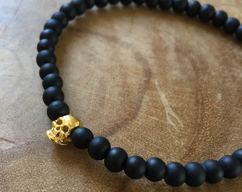 Black Gold Skull: an elastic beaded bracelet with gold skull and matte black glass beads.