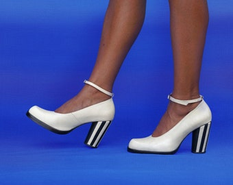 Clara court is a stunningly simple court shoe with sculpted toe shape, ankle strap and striped heel detail.