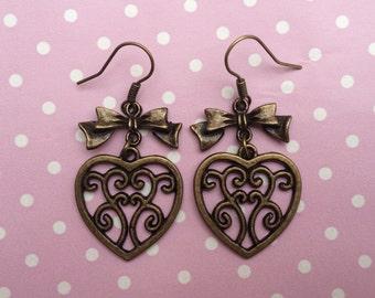 Bronze filigree heart dangle earrings with bronze bows.