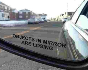 A Pair Of  Objects in Mirror are Losing side mirrors.