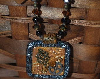 Square polymer clay pendant with four dangling accents