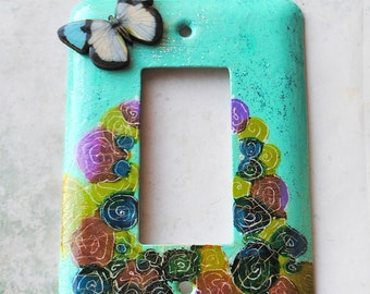Summer Garden, light switch cover, mixed media, stylized flower garden, wooden butterfly focal piece, turquoise, yellow, pink, blue