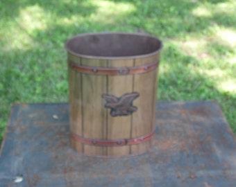 Metal trash can J.L. Clark with wood grain look and copper colored bands on top and bottom with Bald Eagle decorating one side 12.75 in tall