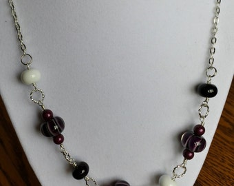 Lamp work bead necklace done in purple and black