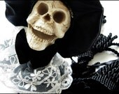 Skull Headed Hanging Tassel Doll in Large Black Hat with White Flowers and Lace Collar