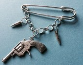 Kilt pin brooch with gun and bullet charms and chain silvertone charms and kilt pin 2.5 inches (6 cms)