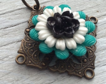 Antiqued brass pendant with black white and teal flowers 45mm