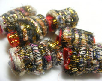 Curiously, we appear to be woven where none of the other beads are. Distinctive, huh? Fiber Beads, textile art beads, artisan hair tube
