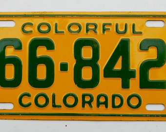 Vintage, mid-century bicycle license plate. Colorful Colorado 1953. Yellow and green.