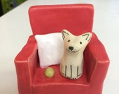 Cute Little White Dog Sitting on a Red Chair Ceramic Sculpture