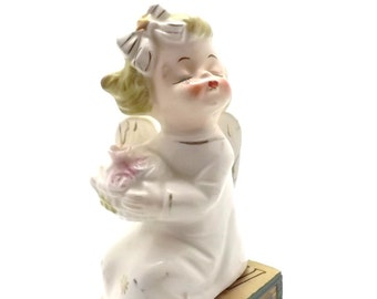 kissing angel girl, shelf sitter, antique porcelain figurine by Commodore