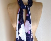 An elegant Anne Klein signed long scarf in purples and dark blue, with a flower pattern.