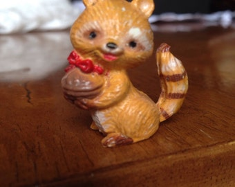 Vintage super cute Plastic Racoon holding a present ( nut)