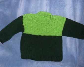 Size 6-9 months green sweater with basket weave pattern.