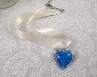 Blue, Heart-shaped lamp work glass drop pendant necklace on a off-white multi-ribbon